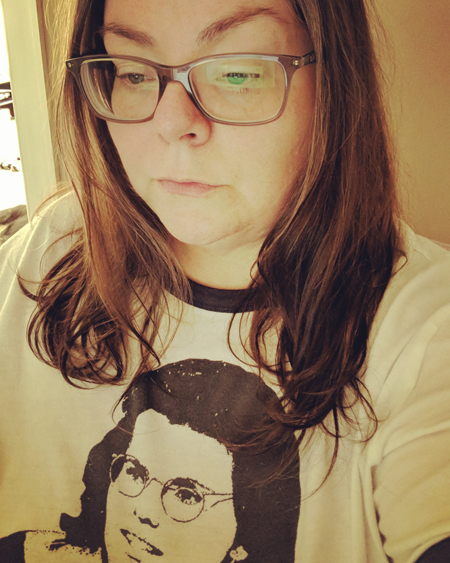 image of me from mid-chest up, sitting at my desk, wearing glasses and a t-shirt with Billie Jean King on it