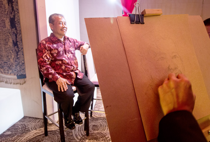 Indonesian Consul General Berlian Napitupulu poses for a live sketch by Tabula Rasa artists