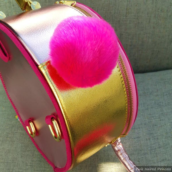 pink fluffy pom pom tail on side of round bag