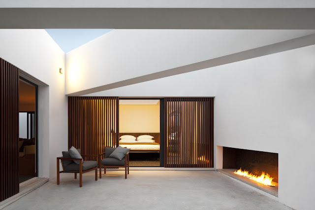 Picture of modern bedroom as seen from the terrace with outdoor fireplace