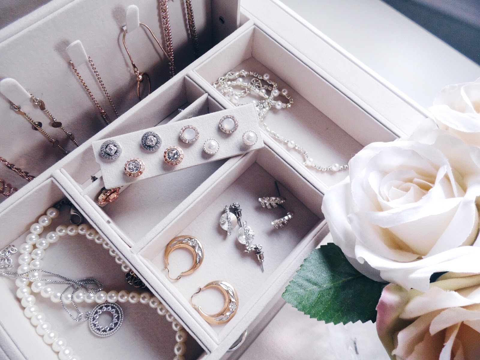 close up of jewerly box with earrings, necklaces and bracelets inside