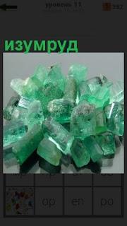На поверхности стола лежат несколько изумрудов зеленого цвета