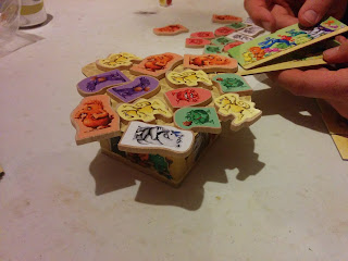 A small cardboard 'table' with an irregularly shaped tabletop. There are several wooden tokens, each adorned with a sticker of various monsters, arranged on top of this cardboard table. You can see some more of these tokens lying nearby. The hands of a player can be seen, holding the monster pusher, which consists of two rectangular pieces of cardboard, each decorated with monsters pushing at one another. The longer of the pieces is held in one hand, with a wooden monster token lying on it, and the smaller piece is used to push the wooden monster token off the bottom piece and onto the cardboard table.