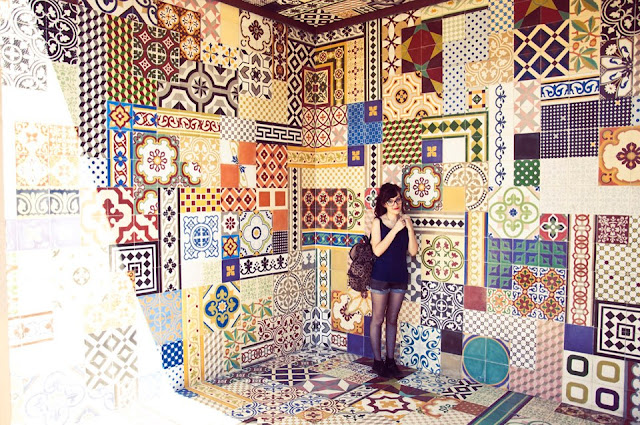Foto onde mostra a fotografa em um local fechado. As paredes são cobertas por azulejos bem coloridos.