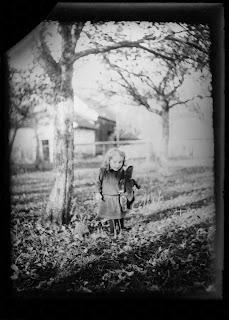 junges Mädchen mit Kuscheltier im Garten - um 1910