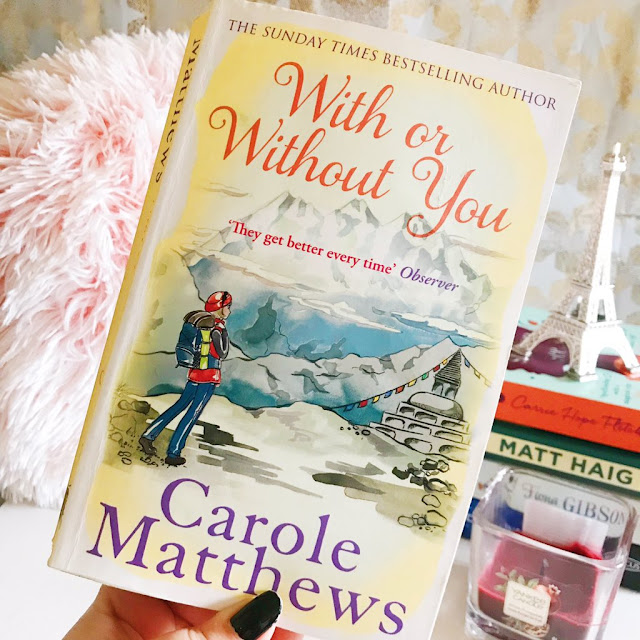 book being held up in front of a background - pink fluffy pillow on left side, stack of books to the right, yankee candle also