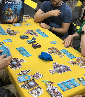 A game of Oceanos in progress at Gen Con. Four people sitting around a table with their first row of ocean cards in front of them, and their modular submarine tiles nearby.