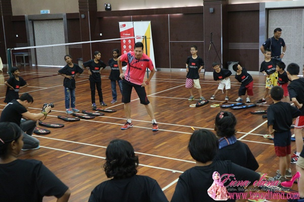 Coach Hafiz Hashim warming up before the badminton clinic session with the children.