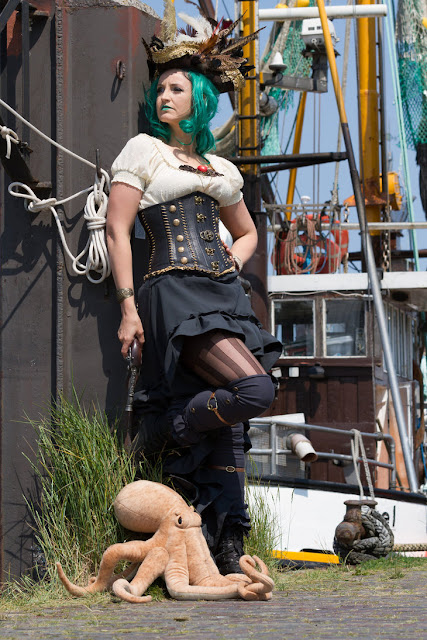 Female steampunk pirate with green wig, green lipstick, black high low hem skirt, ivory blouse, stockings, boots, underbust corset, tricorn pirate hat and pet squid/octopus.