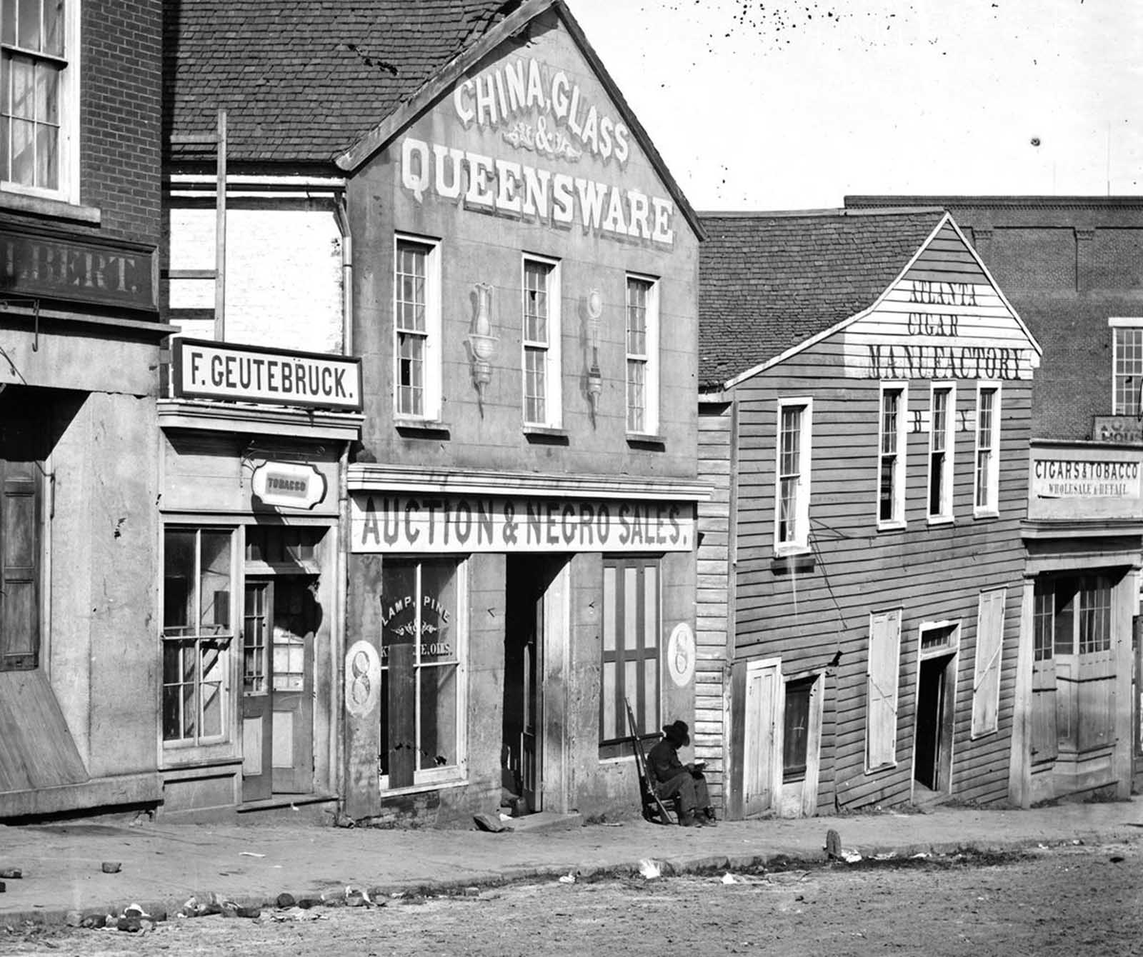A black Union soldier sits, posted in front of a slave auction house on Whitehall Street in Atlanta, Georgia, in 1864. The sign reads