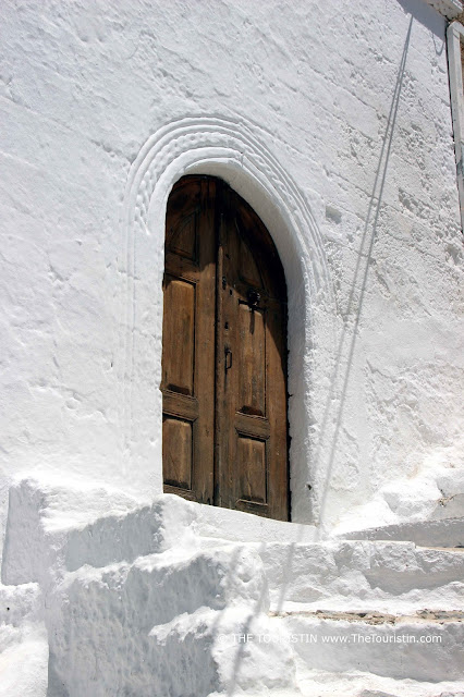 A white-painted staircase leading to a wooden door of a white cubic house.