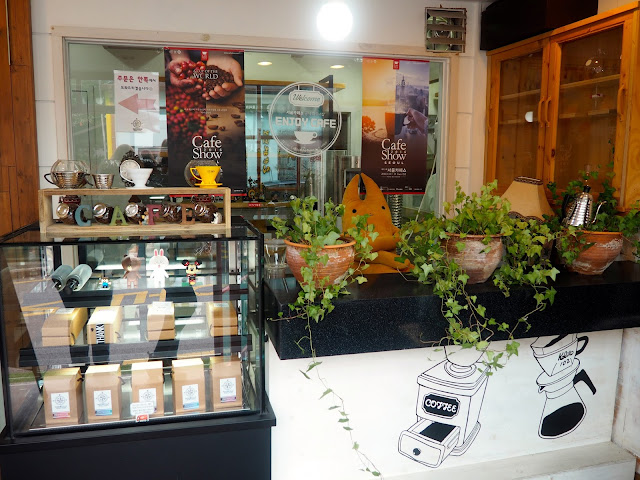 Cafe entrance interior details - coffee bean display and plant pots in Marisstella cafe in Myeongnyun, Busan, South Korea
