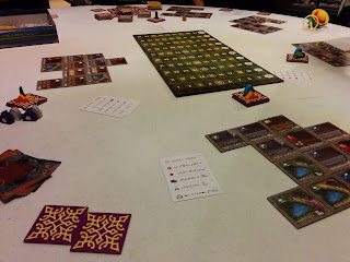 A game of Between Two Cities in progress: the scoring board is in the centre, with the square tiles that form the cities in groups around the edge of the playing area. Stacks of unused tiles, marked with player pieces, sit nearby.