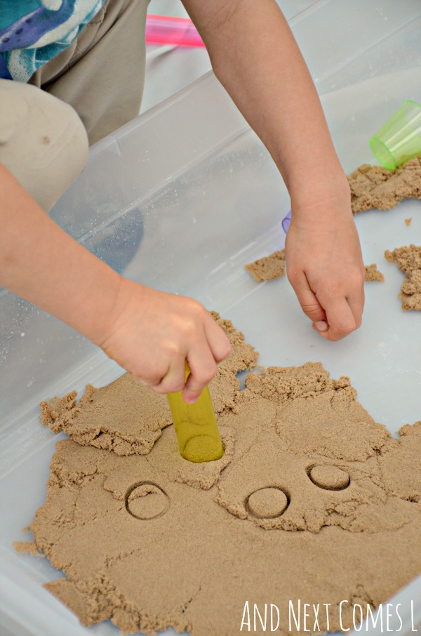 Fine motor activity using kinetic sand and colorful cups that's perfect for toddlers and preschoolers