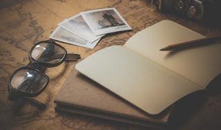 foto libro occhiali e carta geografica