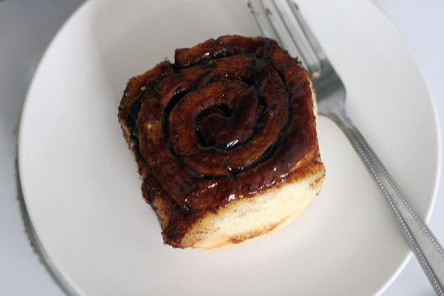 cinnamon bun on a white plate with goo dripping down and a fork to the right
