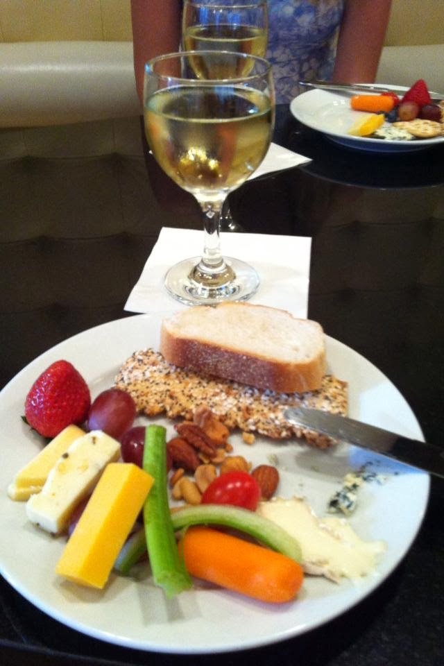 a plate of cheese, fruit and bread and a glass of wine