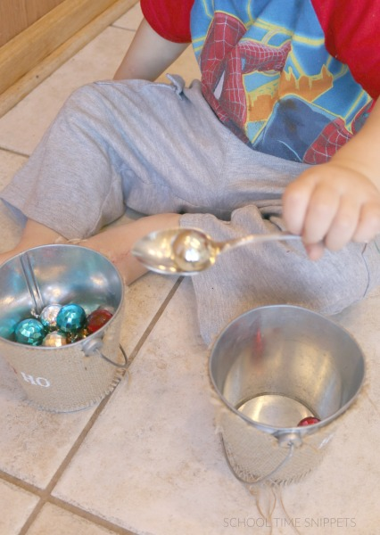 scooping christmas bulbs for fine motor skills development