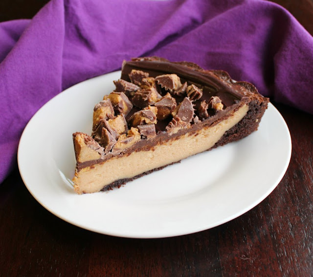 slice of brownie tart filled with peanut butter cheesecake and topped with ganache and chopped peanut butter cups