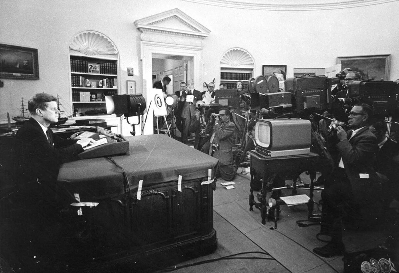 U.S. President John F. Kennedy speaks before reporters during a televised speech to the nation about the strategic blockade of Cuba, and his warning to the Soviet Union about missile sanctions, during the Cuban missile crisis, on October 24, 1962 in Washington, DC.