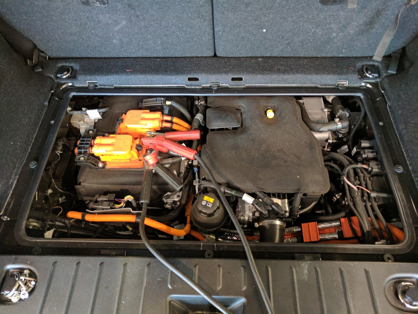 An i3 with the range extender option exposed. The electric motor and power  electronics are on the left, with the jumper cables attached.