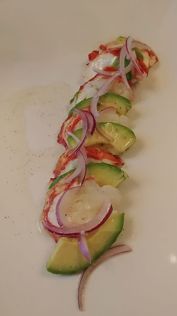chilled lobster tail with avocado vanilla bean lime vinaigrette on a white plate