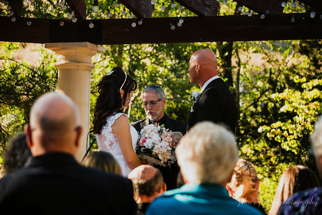 A bride and groom stand with their officiant at their wedding in Colorado