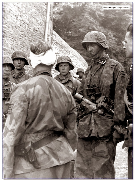 Waffen SS Colonel Max Wunsche, commander of the 12th SS Regiment of the Hitlerjugend Division (bandaged head) with men of the 25th regiment of the SS at Po (village in France) on June 9, 1944. Partly seen on the right side of the image is Rudolf, son of German foreign minister von Ribbentrop