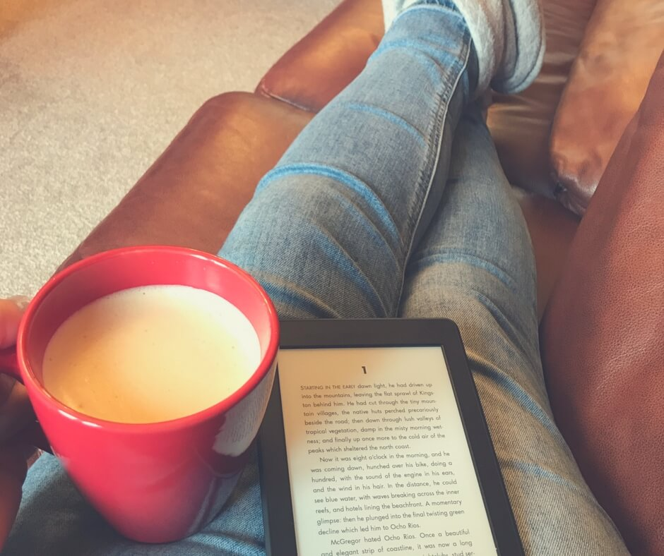 A woman sits on a sofa with her legs up. She is holding a coffee and a kindle - ready to read.