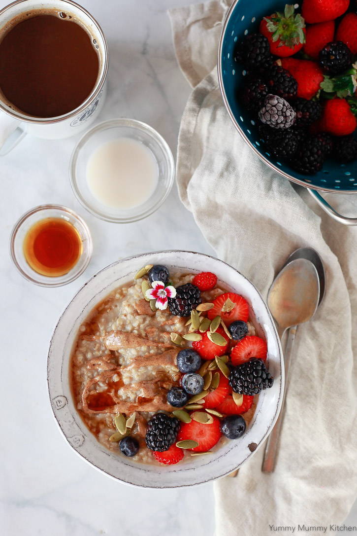 A beautiful bowl of steel cut oats with almond butter, maple syrup, and fresh berries. Slow cooker or Instant Pot steel cut oats is so easy to make.