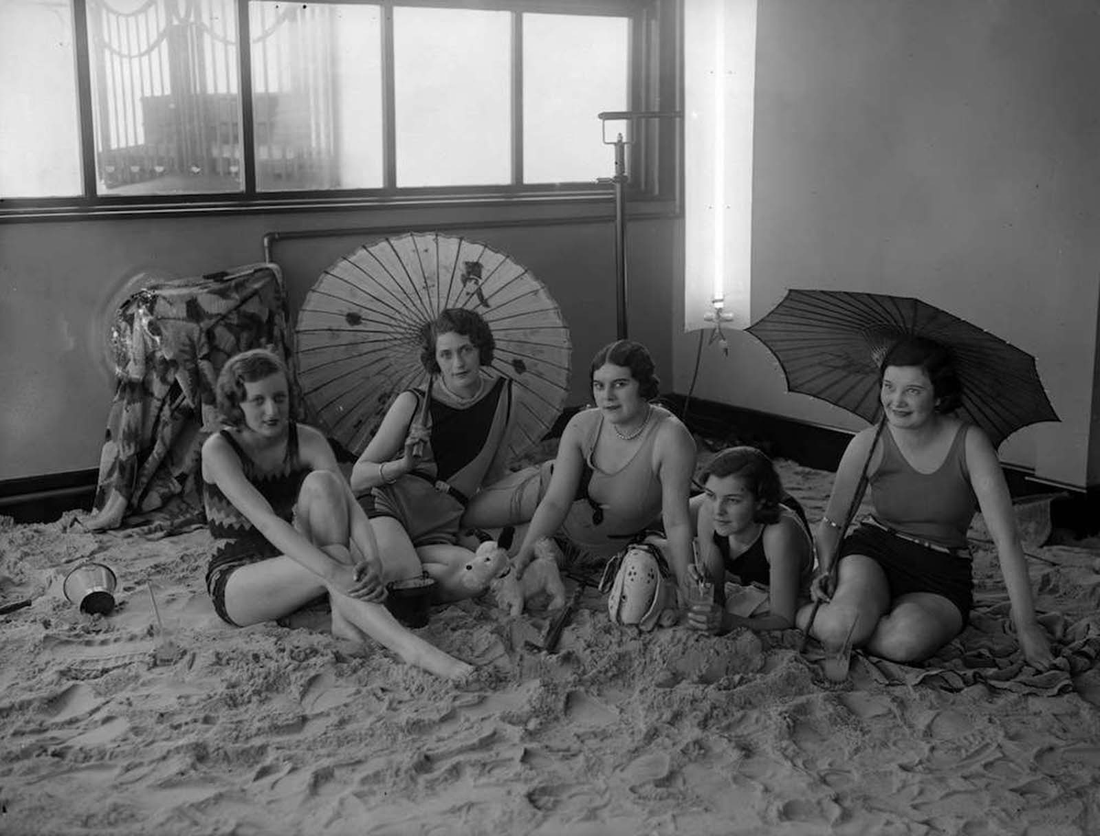 group of ladies relax on the sandy floor in the solarium of the Tolland Hotel, Bournemouth. 1930.