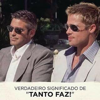 """Foto ao ar livre em dia ensolarado de dois astros do cinema sentados lado a lado: à esquerda, George Clooney e à direita Brad Pitt, ambos com óculos escuros e discreto sorriso nos lábios. George é um homem de pele branca,  rosto oval, cabelos castanhos claros lisos com madeixas grisalhas, nariz afilado, lábios médios, bigode e barba por fazer; usa um paletó cinza sobre camisa branca. Brad é um homem de pele clara, rosto oval, cabelos lisos louros com luzes douradas, nariz levemente arrebitado, lábios médios, bigode e barba por fazer; usa um paletó gelo sobre camisa listrada em branco e azul. Abaixo em letras maiúsculas pretas e entre aspas em negrito, lê-se:  Verdadeiro significado de """"TANTO FAZ!"""""""