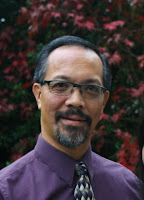 Picture of author Stephen De La Vega, man standing in front of foliage wearing a purple shirt and black and white neck tie