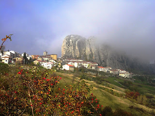 Shrouded in low cloud here, Pizzoferrato sits on a hillside  at the foot of a massive rock formation.