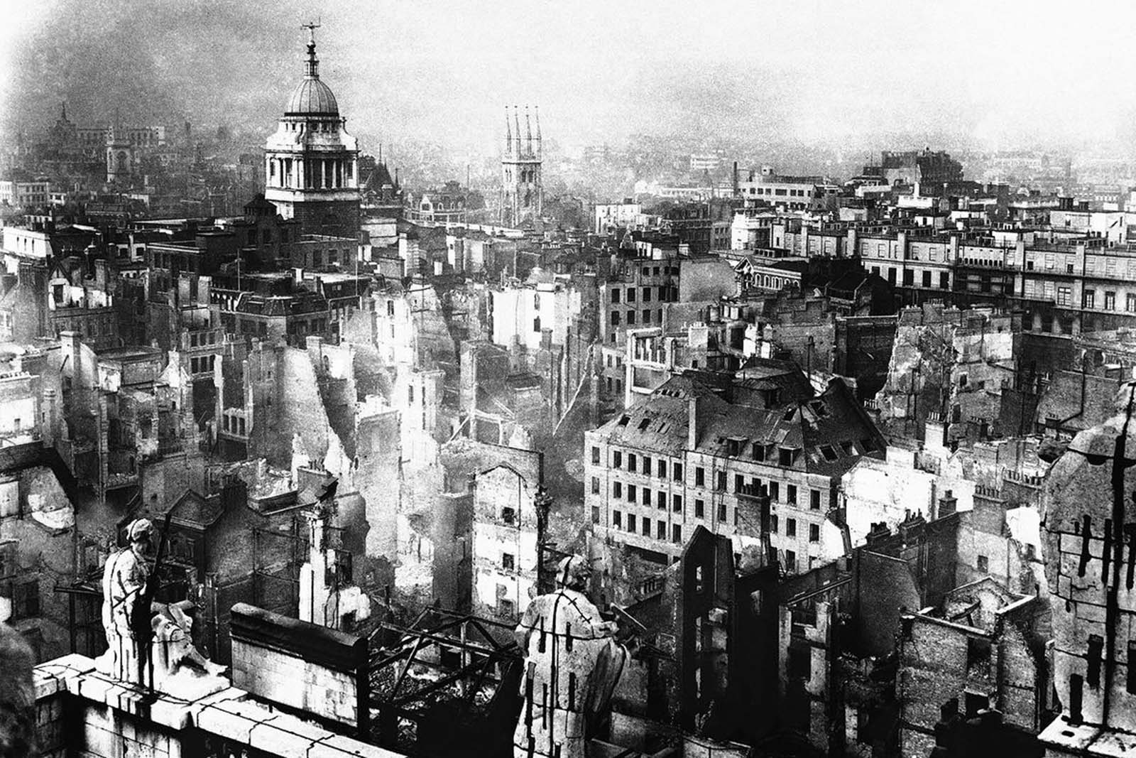 A view from the roof of St. Paul's Cathedral in London in January, 1941, showing how the famous building was ringed by fires on the night of the great Blitz. Devastated buildings are seen on every hand, with the tower of the Old Bailey, surmounted by its statue of Justice, still standing to the upper left.