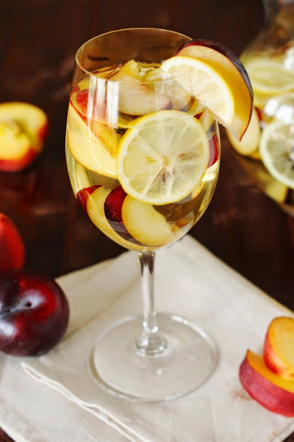 Wine Glass of White Wine Sangria with Nectarines, Plums and Lemons Image