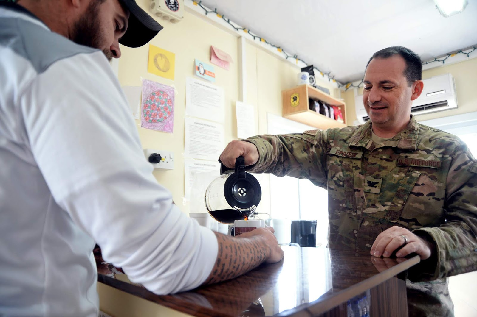 a man in military uniform pours coffee into a cup held by a man in civilian attire