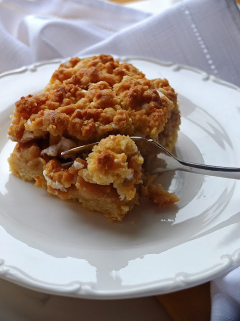 A dessert fork cutting a piece of apple pie with meringue and crumble.