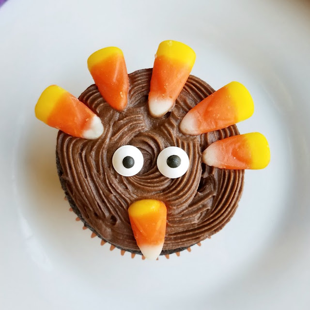close up of cupcake decorated like turkey with candy corn and eye sprinkles
