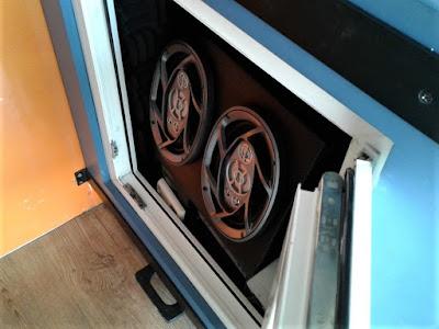 Caixa de som acondicionada em bancada de demonstração fechada com esquadria de PVC demonstra a eficiência desse tipo de material para isolamento acústico.