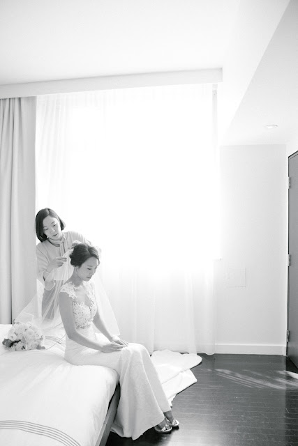 A bridesmaid adjusts the bride's veil as she sits on the bed | Karen Hill Photography