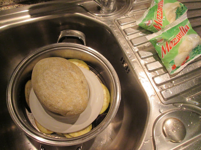 Fatias de berinjela salgada escorrendo no escorredor de macarrao com um prato em cima e sobre o prato uma pedra.