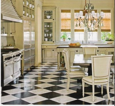 This wide open family style kitchen looks grand and elegant with the black and white tile floor and glass fronted cabinets