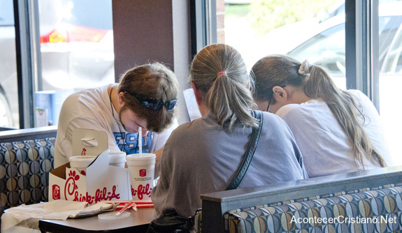Cristianos orando en restaurante antes de comer