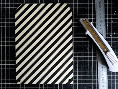 Rectangular piece of plywood bunting, printed with black stripes, laid out on a cutting mat along with a metal ruler and a utility knife.