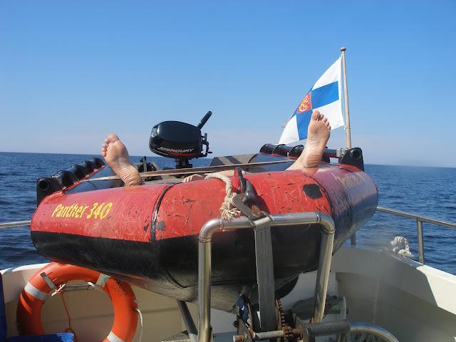 Telineessä veneen päällä olevassa kumiveneessä lepää joku niin että vain jalkapohjat näkyvät