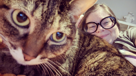 image of me lying on the couch, wearing large black-framed glasses, with Sophie the Torbie Cat lying in front of me, very close to the camera