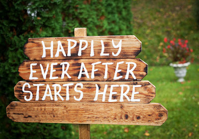 A rustic wooden sign made from old fence posts has 'Happily Ever After Starts Here' written on it in white paint.