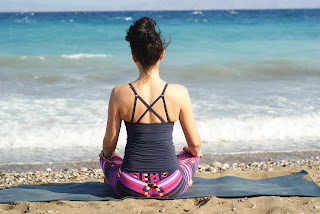 woman meditation on beach with ocean in back ground