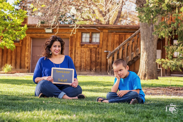"""A sister hold a """"brother for sale"""" sign for a family portrait session"""
